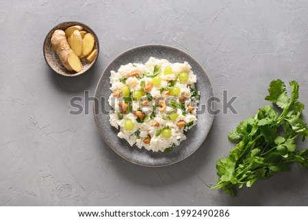 Curd Rice with cashews, grapes, cilantro on a grey background. Indian South cuisine. Top view. Stok fotoğraf ©