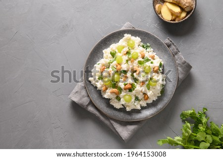 Curd Rice with cashews, grapes, cilantro on a grey background. View from above. Copy space. Indian South cuisine Stok fotoğraf ©