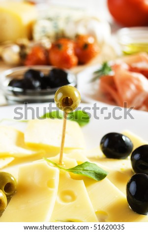 Cured cheese with green and black olives served as appetizer