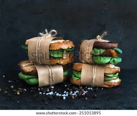 Cured chicken and spinach whole grain sandwiches placed one on another wrapped in craft paper and tied with a decoration rope  with spices and black stone background