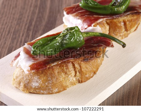 Cured ham and Pepper �montadito� . Montadito is an appetizer or snack (Spanish Tapa) made with a slice of bread with some other food on it.