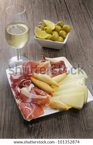 cured iberian ham and cheese tapas with sherry wine and olives