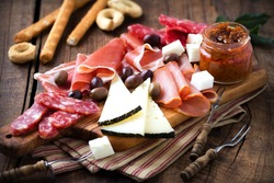 Cured meat and cheese platter of traditional Spanish tapas - chorizo, salsichon, jamon serrano, lomo and slices of goat cheese - served on wooden board with olives and bread sticks