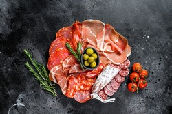 Cured meat platter of traditional Spanish tapas. Chorizo, jamon serrano, lomo and fuet. Black background. Top view.