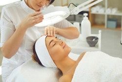 Curing skin problems. Cropped female cosmetologist looking at client's face through magnifying lamp examining her skin. Happy relaxed young woman getting professional facial treatment in spa salon