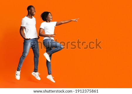 Curious african-american couple jumping up and cheerfully pointing away at empty space, orange studio background. Emotional young black man and woman aiming at advertisement, full length photo