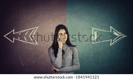 Curious and doubtful young woman, has to choose right or left side. Puzzled student girl in front of a split blackboard with arrows showing two different directions. Choice concept, difficult decision Photo stock ©