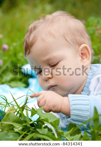 curious baby boy touching grass and thinking