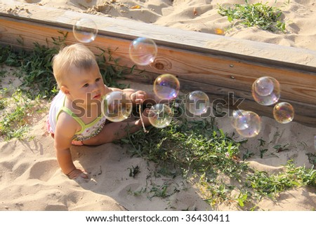 Curious baby looking at soap bubbles