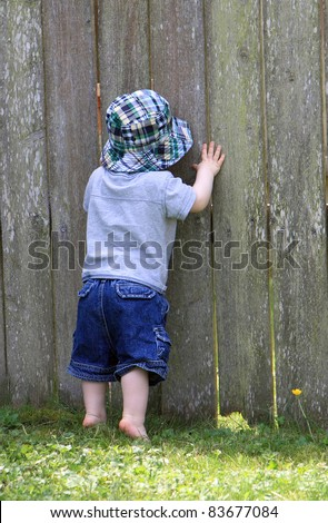 Curious boy peeks through hole in fence to see what is on other side
