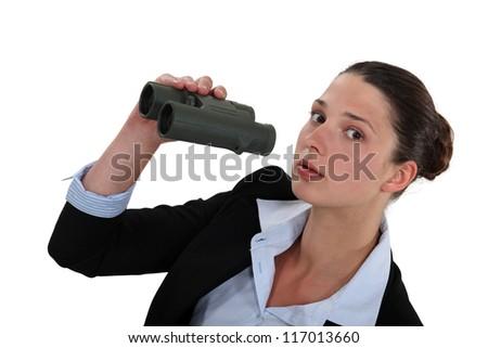 Curious businesswoman holding pair of binoculars