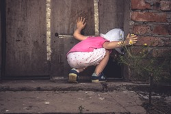 Curious child lookinginto dark hole in barn door in countryside shed concept curiosity