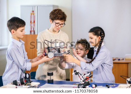 Curious clever pupils with the help of their female teacher doing a group project programming homemade robot using laptops on extracurricular classes
