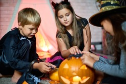 Curious concentrated friends sitting on floor and enjoying game with Halloween toys such as jack-o-lantern and spiders telling scary stories to each other