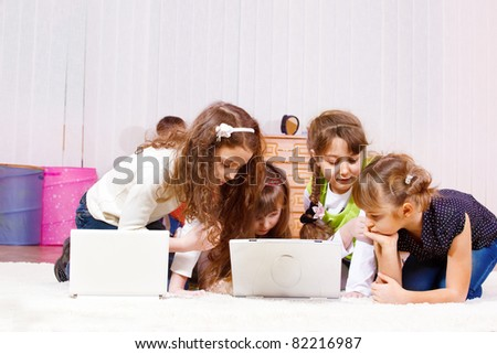 Curious elementary school-aged girls busy playing computer games