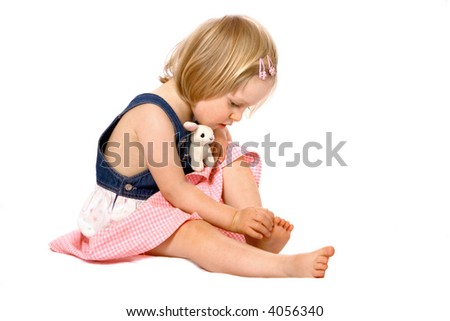 Curious girl toddler examines her toes, isolated on white.