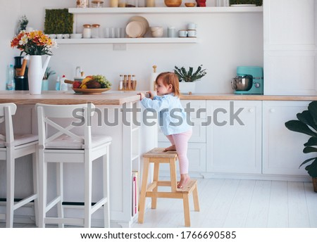 curious infant baby girl trying to reach things on the table in the kitchen with the help of step stool