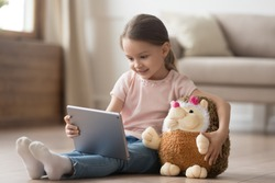 Curious little child girl having fun using digital tablet alone embracing toy sitting on floor, happy preschool smart kid playing with computer looking at screen watching cartoons online at home