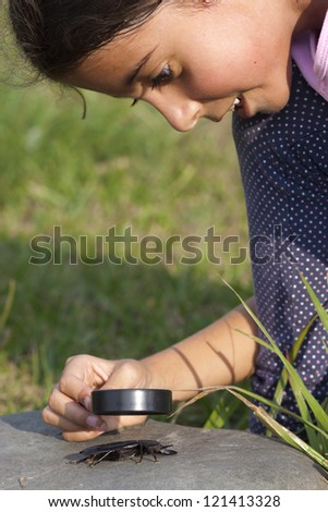 Curious Little Girl Looking At Beetle Through Magnifying Glass Outdoor