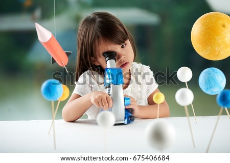 Curious little girl looking through microscope while having fun in scientific club for preschoolers, blurred background #675406684