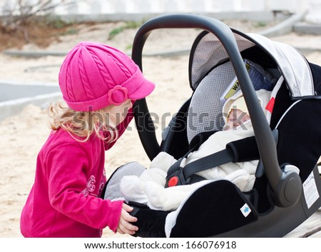 Curious Little Girl Looks In A Car Seat Where Sleeping Brother 166076918