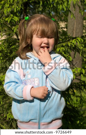 Curious little girl standing near pine tree her eyes are closed because of sunlight