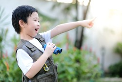 Curious little young Asian boy holding a binoculars and point finger out in the garden. Exploring the world, outdoors activity. Feeling fun. Boy wear green outdoors vest. Holiday, education concept