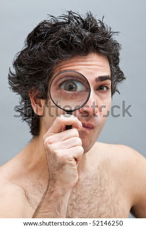 Curious man holding a magnifier over his eye