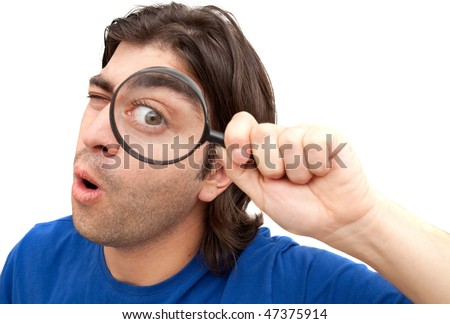 Curious man holding a magnifying glass over his eye