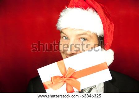 Curious man holding present voucher wearing santa hat