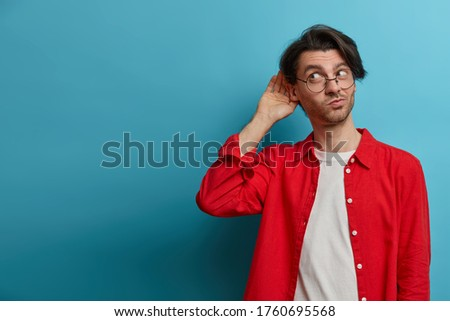 Curious man likes gossips, wants to overhear secret information, wears optical glasses and red shirt, tries to hear womans phone conversation, listens attentively keeps hand near ear for eavesdropping Foto stock ©