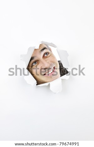 Curious man looking up through hole ripped in white paper