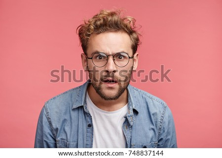 Curious scrupulous male model with trendy hairrdo and beard looks attentively at one point, sees something strange or suspicious. Angry man tries to overhear wife`s talk, looks annoyed, feels jealous Foto stock ©