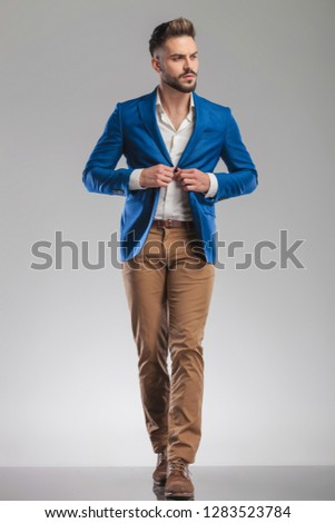 curious smart casual man buttons suit while walking forward on light grey background and looks to side #1283523784