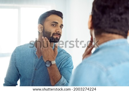 Curious thoughtful indian man standing in front of mirror touching beard on face looking at reflection. Thoughtful young adult eastern guy with bristle engaged in morning facial skin care routine Сток-фото ©