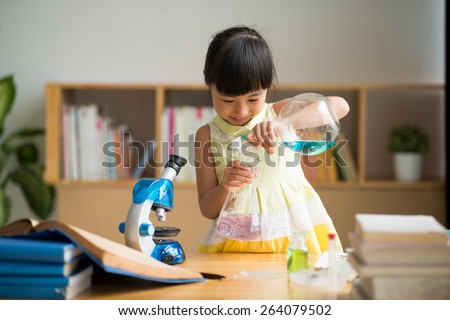Curious Vietnamese girl pouring reagent into flask