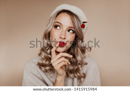 Curious well-dressed girl thinking about something with smile. Indoor portrait of amazing white lady in brown beret enjoying photoshoot