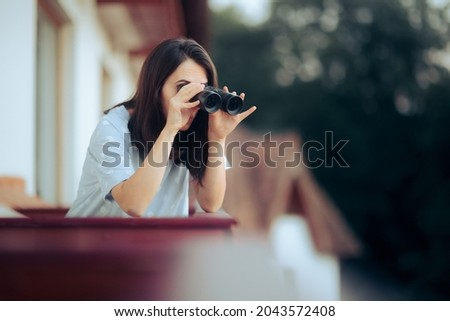 Curious Woman Holding a Pair of Binocular Spying on her Neighbors. Funny young person snooping and peeping from her balcony  Foto stock ©