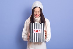 Curious woman with bright red lips and looking in her striped blackand whirte bag with inscription sale. Studio photo of emotional girl wearing white warm clothing isolated over blue background.