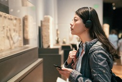 curious young asian chinese woman tourist looking at exposition in museum using headphones and listening audio guide in modern gallery. Education and entertainment concept. traveler in art center
