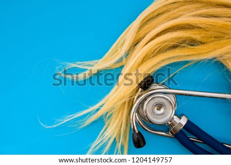 Curl human hair color blonde and stethoscope on blue background occupy half of photo, in second half - empty space for titles. Concept photo of medical and cosmetic hair care, treatment of diseases #1204149757