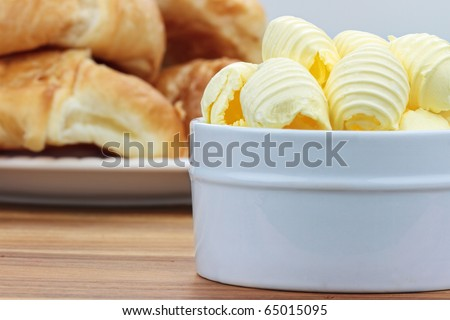 Curled butter in a dish with croissants in the background.