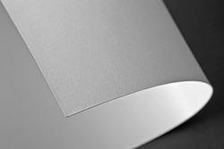 Curled corner of white paper. Mock up. Close up. Macro shot