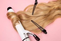 Curling blonde hair on a large diameter curling iron on a pink background. Curl care, hair styling, black clips.