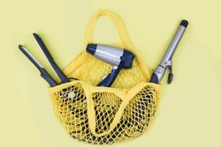 curling iron, hair dryer, straightener are in a yellow purse. Shopping bag with hairdresser items