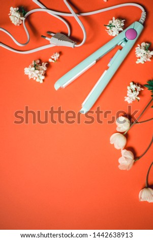 Curling iron ripple on a coral background. Hair accessory on orange background with flowers. Hairstyle tool
