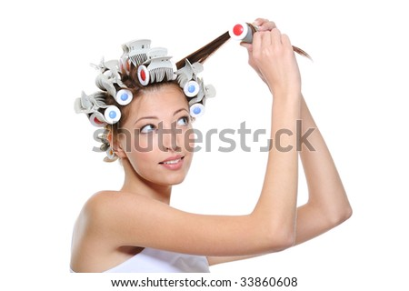 curling of hair by the young beautiful woman - white background