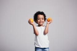Curly African American boy in a white T-shirt holds two oranges in his hands and smiles on a gray background.