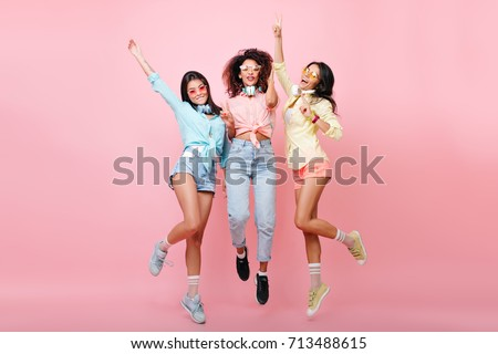 Photo of  Curly african woman in jeans jumping while posing with international university friends. Tanned latin girl in yellow shirt dancing on pink background and having fun with other ladies.