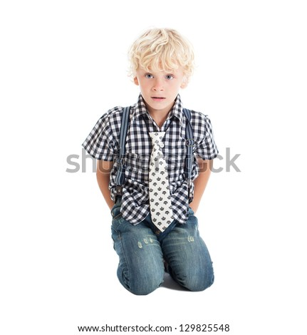 Curly blond boy sitting on the floor on his knees. The boy hiding his hands behind his back. Studio shot, isolated on white background.